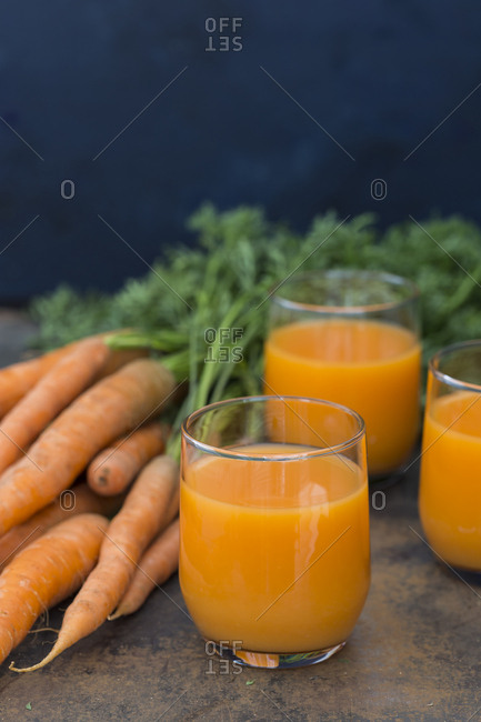 Three glasses of fresh carrot juice and carrots