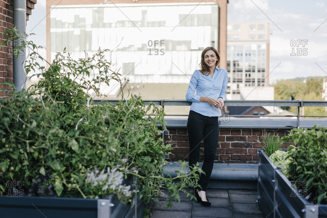 Businesswoman standing on her urban rooftop garden