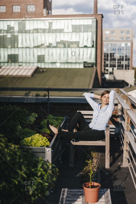 Businesswoman relaxing in his urban rooftop garden