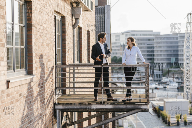 Business people standing on balcony, discussing