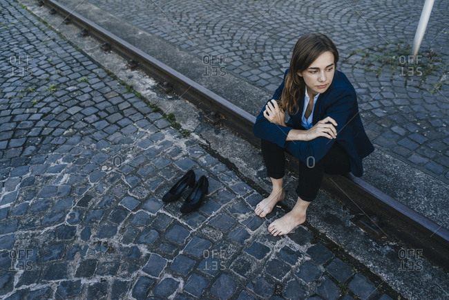 Barefoot businesswoman sitting on rail