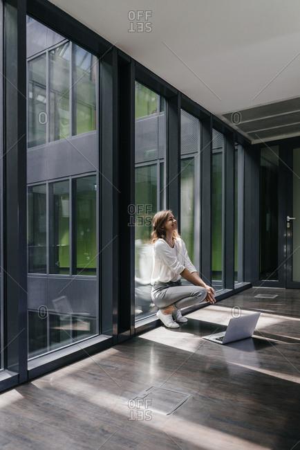 Happy businesswoman crouching on floor