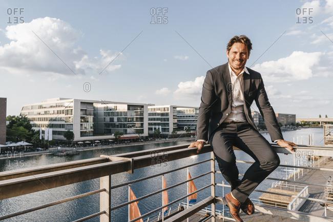 Confident businessman sitting on railing of balcony