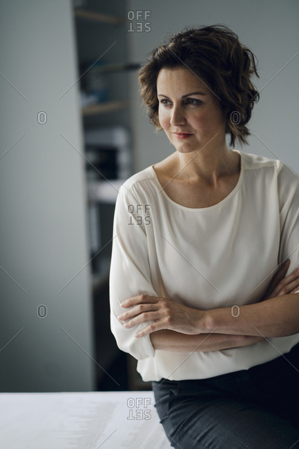 Mature businesswoman sitting in office with arms crossed