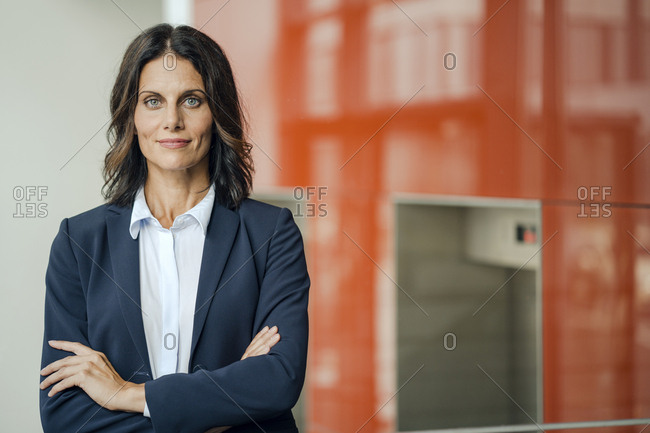 Portrait of a successful businesswoman, standing in front of elevator, with arms crossed
