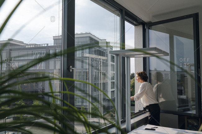 Businesswoman standing in office, looking out of window