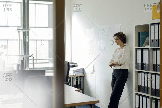 Businesswoman leaning against wall in office, with arms crossed