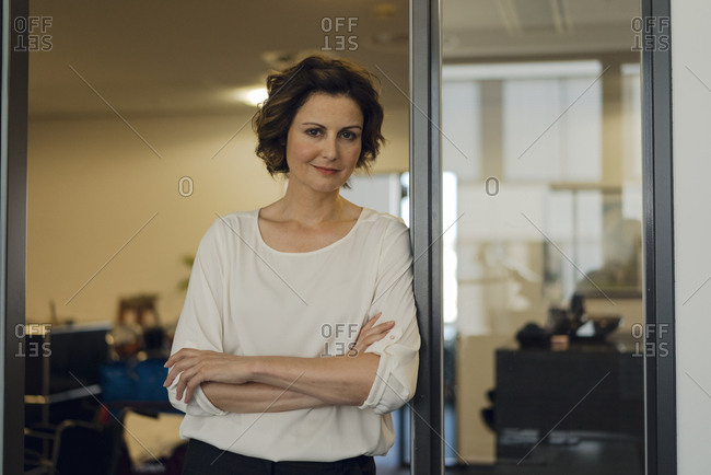 Successful businesswoman leaning in glass door, with arms crossed