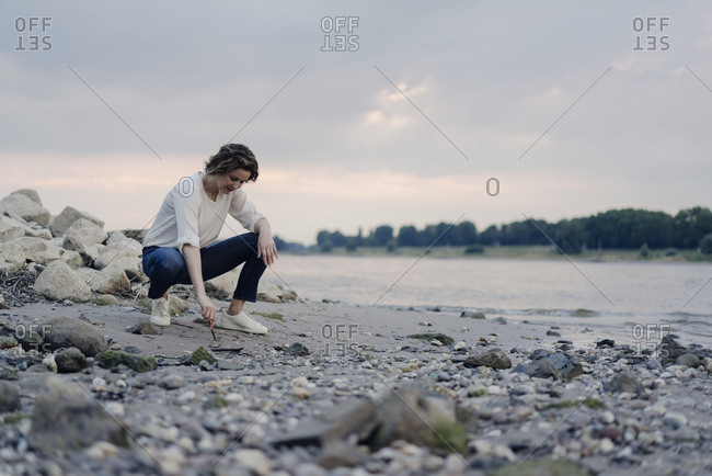 Woman crouching at the riverside, drawing in sand with a stick