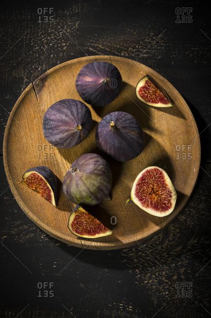 Figs on wooden plate, dark wood