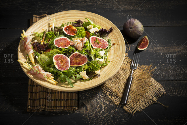 Mixed salad with figs, tomatoes, sheep cheese, grissini with ham on bambus plate