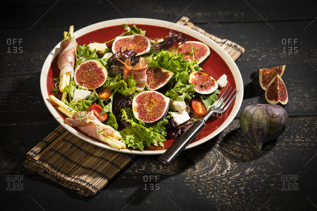 Mixed salad with figs, tomatoes, sheep cheese, grissini with ham on plate