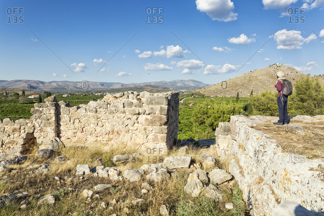 Greece, Peloponnese, Argolis, Tiryns, archaeological site, Cyclopean masonry. castle wall, Tourist looking at view