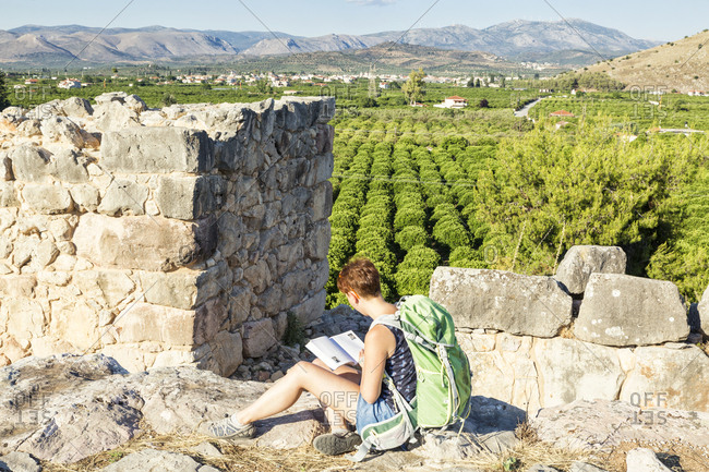 Greece, Peloponnese, Argolis, Tiryns, archaeological site, female tourist reading guide book