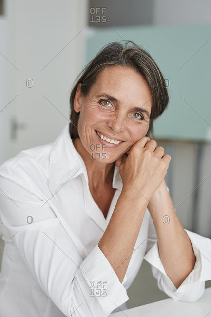 Portrait of smiling mature businesswoman wearing white blouse