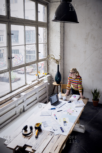 Woman standing at desk in a loft looking through window