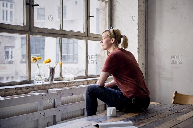 Woman sitting on desk in loft looking through window