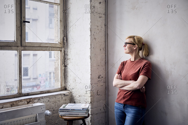 Smiling woman leaning against wall in loft looking through window
