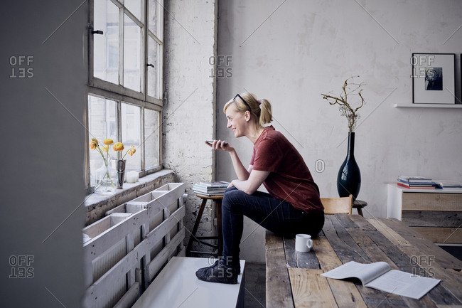 Woman sitting on desk in loft using cell phone