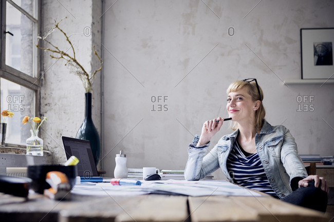 Portrait of smiling woman sitting at desk in a loft