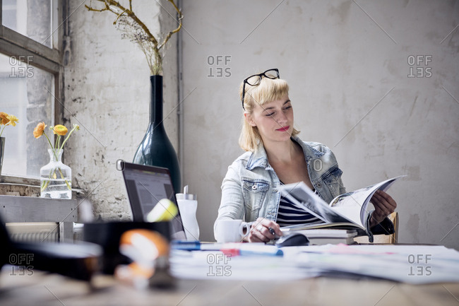 Portrait of smiling woman sitting at desk in a loft leafing through book