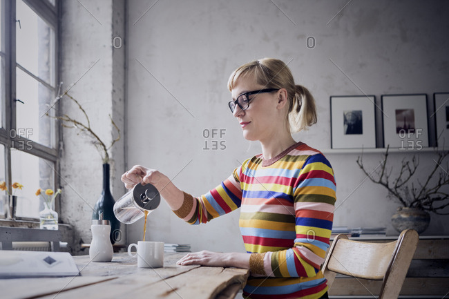Woman pouring coffee in a mug at desk in a loft