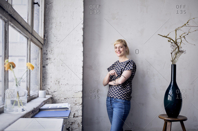 Portrait of laughing woman leaning against wall in loft