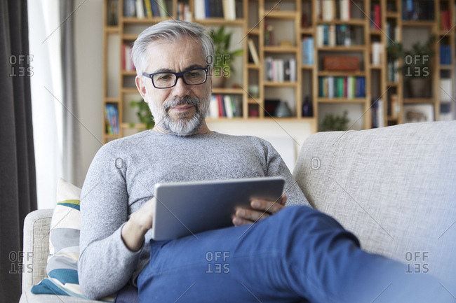 Portrait of mature man sitting on couch at his living room using tablet