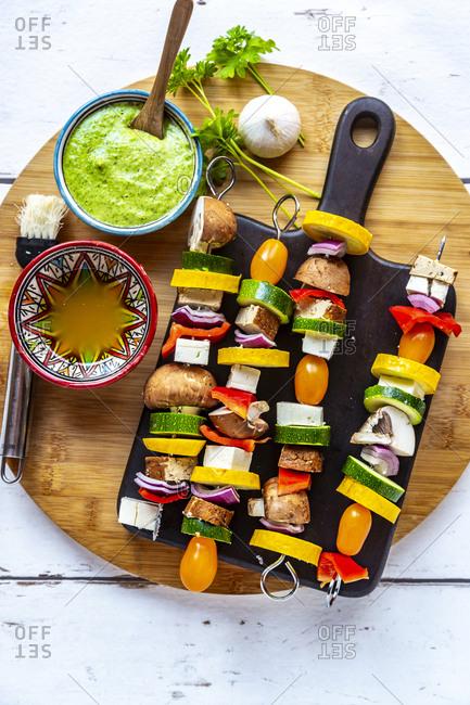 Vegetarian grill skewers, tomato, yellow and green zucchini, tofu, feta, onion and champignon, Argentinian chimichurri