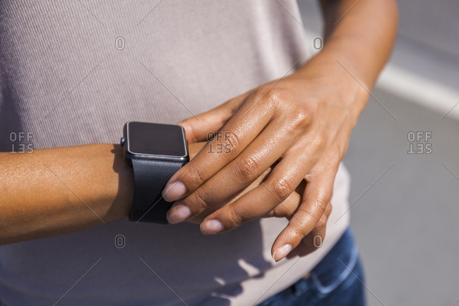 Woman's hand adjusting settings of smartwatch, close, up