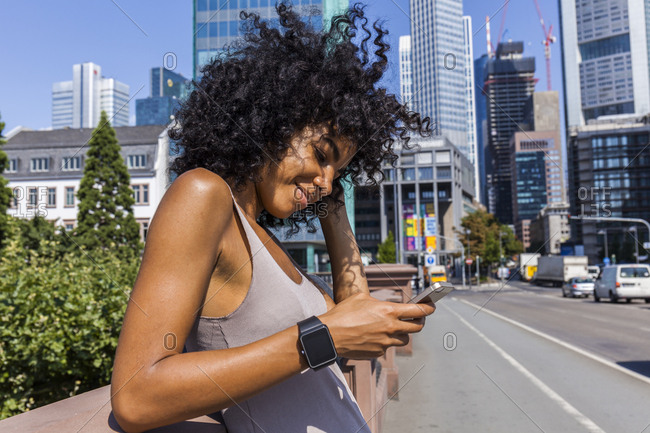 Germany, Frankfurt, portrait of smiling young woman with curly hair using cell phone in the city