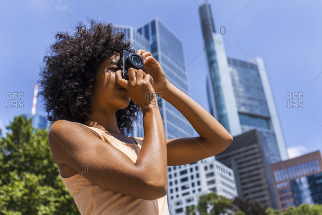 Germany Frankfurt Young Woman With Curly Hair Taking Photos In The City Stock Photo