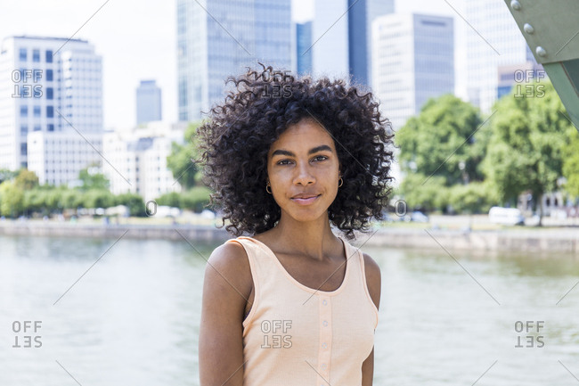 Germany, Frankfurt, portrait of relaxed young woman with curly hair in front of Main River