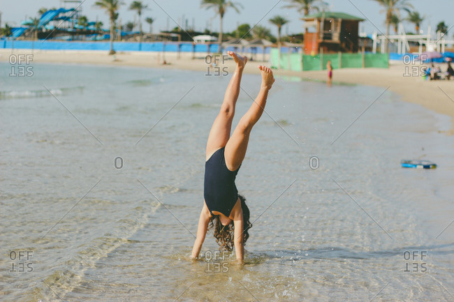 Young girl doing a handstand on the beach while a wave comes in