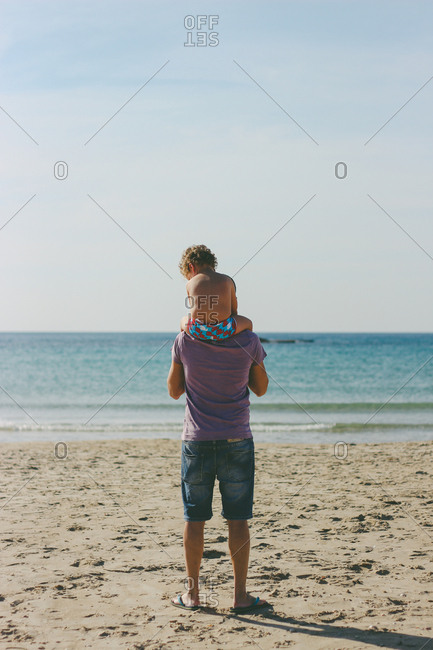 Father with his son on his shoulders looking out at the ocean