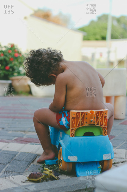 Toddler sitting on a plastic toy in his backyard