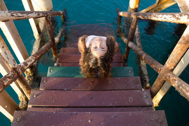 Young girl looking at camera while sitting on stairs that lead into the ocean