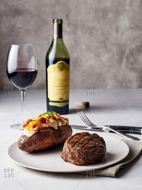 Filet mignon steak served with baked potato and red wine