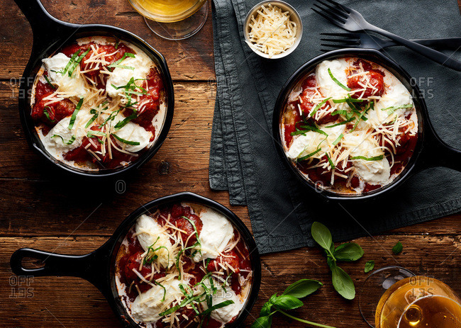Meatballs topped with tomato sauce and cheese served in cast iron skillets