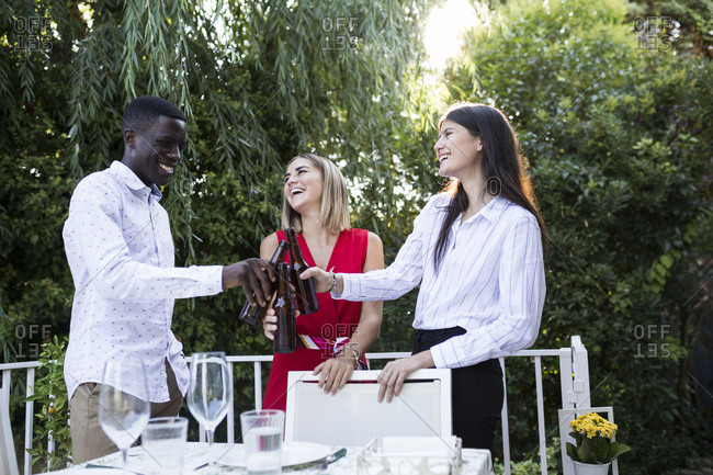 Multiethnic group of friends standing around table in garden and clinking beer bottles smilingly in Madrid, Spain