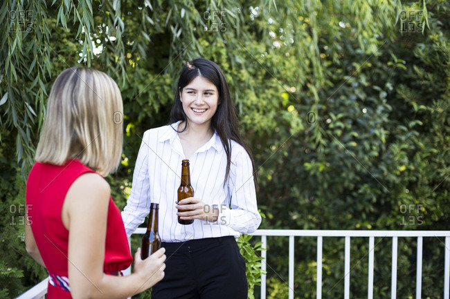 Young women enjoying time together drinking beer and talking in backyard in Madrid, Spain