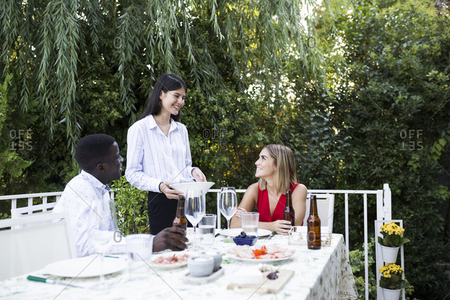 Young woman making preparations for meal in garden and having fun with her friends in Madrid, Spain