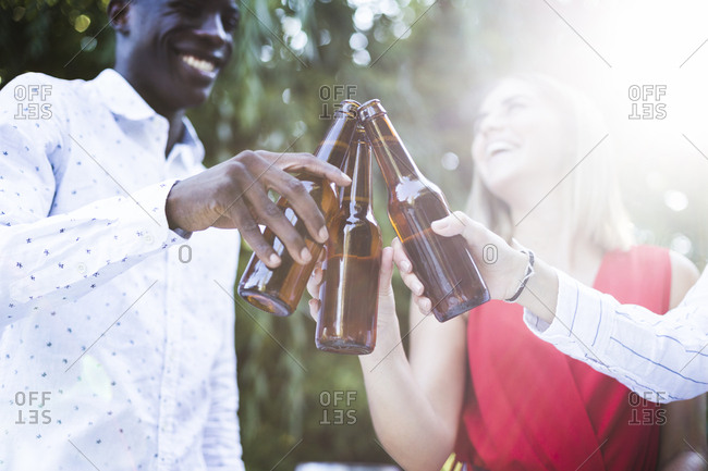 Multiethnic group of smiling friends standing in garden and clinking beer bottles together in Madrid, Spain