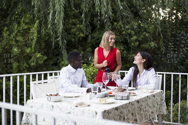 Friends having lunch together in garden while cheerful girl is opening bottle of wine in Madrid, Spain