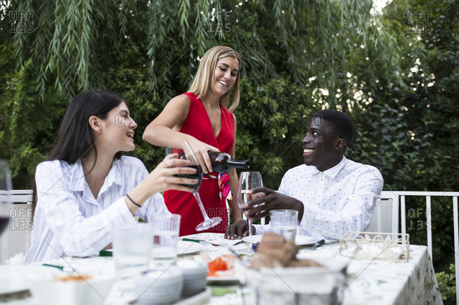 Cheerful woman pouring red wine for friends while having party in garden in Madrid, Spain