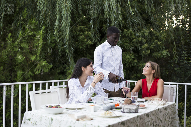 Black man pouring red wine for friends while having party in garden in Madrid, Spain