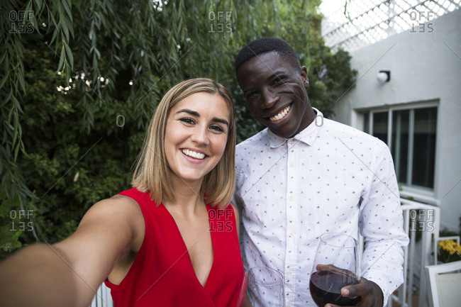 Young woman and black man taking a selfie with a phone while having party in garden in Madrid, Spain