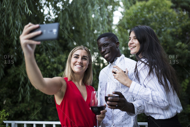 Group of laughing people taking a selfie with a phone while having party in garden in Madrid, Spain