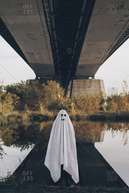 Person dressed up as a ghost standing underneath a bridge