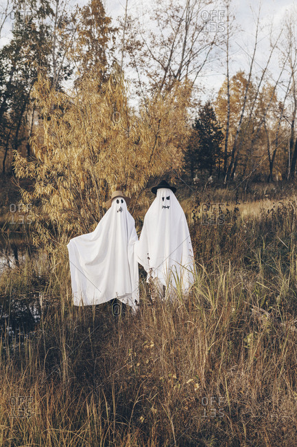 Two people dressed up as ghosts standing in a field